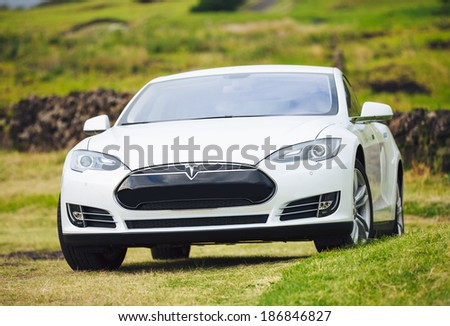 San Francisco, CA - April 2014: Tesla Motors model S sedan electric car on country road, Tesla's new Gigafactory would help Tesla increase its monthly production volume to 20,000 cars per month. - stock photo