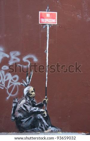 SAN FRANCISCO, CA - CIRCA MAY 2010: Stencil graffiti piece by Banksy on a building on Mission St, circa May 2010 in San Francisco, CA - stock photo