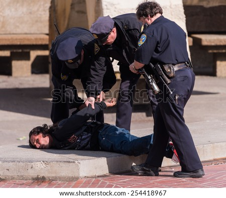 SAN FRANCISCO, CA - February 19, 2015 - San Francisco Police arrest and handcuff homeless man on the street. - stock photo