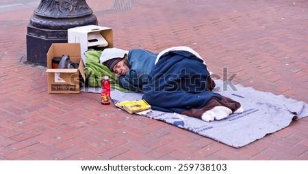 SAN FRANCISCO, CA - March 7, 2015 - A homeless man sleeps on downtown Market Street in San Francisco. - stock photo