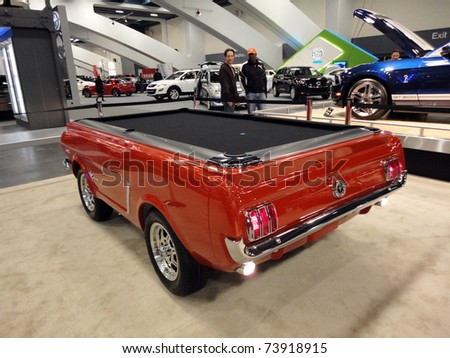SAN FRANCISCO, CA - NOVEMBER 20: People admire a Ford Mustang turned into a Pool table on display at the 53rd San Francisco International Auto Show, on November 20, 2010 San Francisco, California. - stock photo
