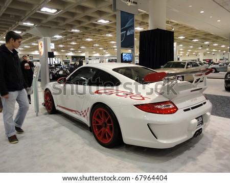 SAN FRANCISCO, CA - NOVEMBER 20: People look at Porsche GT3RS on Display with a racing style paint job at the 53rd International Auto Show, on Saturday November 20 2010 San Francisco California. - stock photo