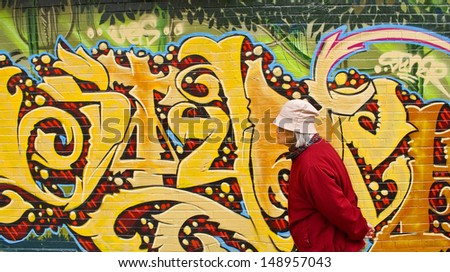 SAN FRANCISCO/CA/USA - CIRCA AUGUST 2010: Elderly Chinese woman passes a wall of graffiti in Chinatown in August, 2010. It's one of North America's largest Chinatowns - and the oldest in the USA. - stock photo