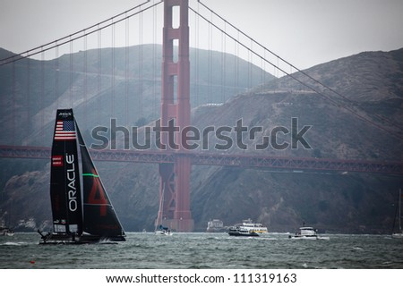 SAN FRANCISCO, CALIFORNIA, USA - AUGUST 25, 2012: Team USA sails past Golden Gate Bridge in the America's Cup Louis Vuitton Cup Sailing races on August 25, 2012 in San Francisco Bay, California - stock photo
