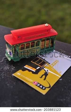 SAN FRANCISCO, California, USA, - NOVEMBER. 16. 2011: Miniature cable car toy and cable car passport, San Francisco's cable car is world's last manually-operated system, icon of San Francisco - stock photo
