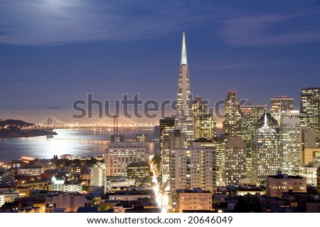 San Francisco financial district at night, with the bay illuminated by the full moon. - stock photo