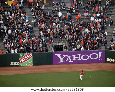 SAN FRANCISCO - JUNE 14: Giants Vs. Orioles: Giants Fan stretches for a homerun ball as the left fielder watches the back fly out of the field.  June 14 2010 Att Park San Francisco California. - stock photo