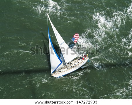 SAN FRANCISCO - MAY  26:close-up aerial view of sailboat racing under Golden Gate Bridge on May 26, 2012 in San Francisco Bay California. San Francisco is currently hosting the 2013 Americas Cup races - stock photo