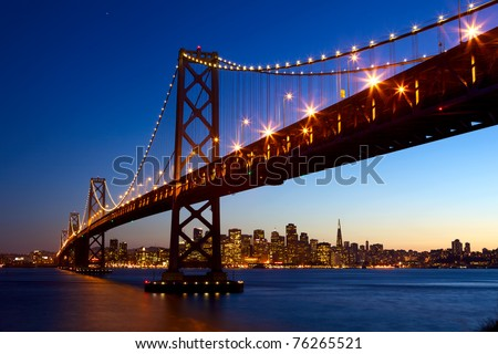 San Francisco skyline and Bay Bridge at sunset, California, USA - stock photo