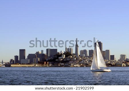 San Francisco Skyline at sunset coming into port, with a sailboat crossing the bow - stock photo