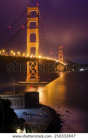 SAN FRANCISCO,USA -MARCH 1 2014:The famous San Francisco Golden Gate Bridge in California,United States of America.Long exposure of Fort Point,the bay and the illuminated red suspended bridge at night - stock photo