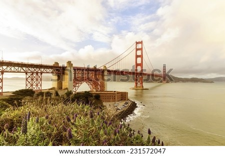 SAN FRANCISCO,USA - MARCH 1 2014: The Golden Gate Bridge in California,United States of America.View of Fort Point, surfers and the red suspended bridge connecting Frisco to Marin County at sunset. - stock photo