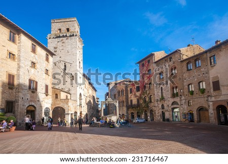 SAN GIMIGNANO, ITALY - OCT 28, 2011: Tourists walk in the Historic Centre of San Gimignano - stock photo