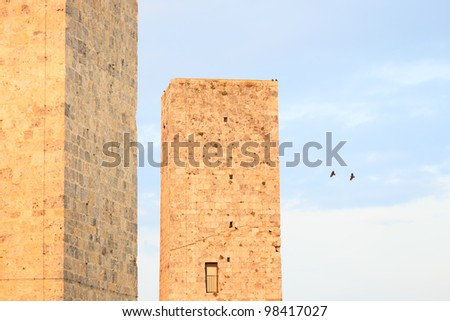 San Gimignano landmark medieval town, Tuscany, Italy, Europe. Two towers detail with two birds flying and others on lower tower. - stock photo