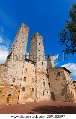 San Gimignano - Siena Tuscany Italy / Three towers and houses in Piazza delle Erbe, San Gimignano medieval town (UNESCO heritage), Siena, Tuscany, Italy - stock photo