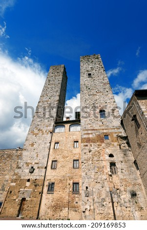 San Gimignano - Siena Tuscany Italy / Two towers and houses in Piazza delle Erbe, San Gimignano medieval town (UNESCO heritage), Siena, Tuscany, Italy - stock photo