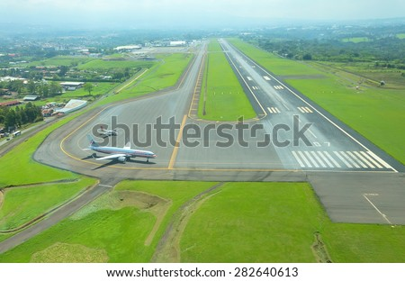 SAN JOSE, COSTA RICA - May 10: Aerial view of runway at Juan Santamaria International Airport on May 10, 2014 in San Jose, the capital of Costa Rica. This airport is the primary airport in the country - stock photo