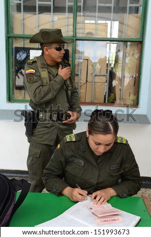 SAN JOSE DEL GUAVIARE,COLOMBIA, NOVEMBER 9: the Colombian Police guard over law and order in the city, checking passports at the airport on November 9, 2012 in San Jose del Guaviare, Colombia - stock photo