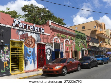 SAN JUAN, PUERTO RICO - MARCH 13, 2015: Facades of bars and restaurants in Calle Elisa Colberg in the Tras Talleres neighborhood. Parked cars, wall paintings and graffiti. Blue sky with white clouds. - stock photo