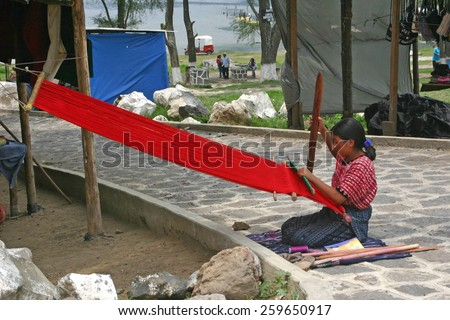 SAN MARCOS LA LAGUNA, GUATEMALA-MAY 15, 2007:  A Guatemalan woman weaves a blanket on a small outdoor loom hoping to sell it to passing tourists.  Weaving is a major activity of local women. - stock photo
