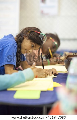 SAN MATEO, CA May 20 2016 - A girl works on an activity during the 11th Annual Bay Area Maker Faire at the San Mateo County Event Center. - stock photo