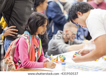 SAN MATEO, CA May 20 2016 - A yong girl receives instructions for a craft project during the 11th annual Bay Area Maker Faire at the San Mateo County Event Center. - stock photo
