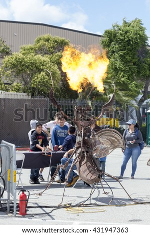 SAN MATEO, CA May 20 2016 - Two boys operate a flaming interactive art sculpture during the 11th Annual Bay Area Maker Faire at the San Mateo County Event Center. - stock photo