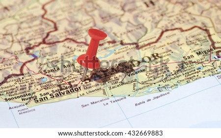 San Salvador marked on map with red pushpin. Selective focus on the word San Salvador and the pushpin. Pin is in an angle and casts some shadow to the right.  - stock photo