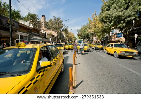 SANANDAJ, IRAN - OCT 9: City traffic with lines of taxi cars of yellow color on October 9, 2014 in Middle East. Capital of Kurdish culture & Kurdistan Province, Sanandaj has population of 380,000   - stock photo