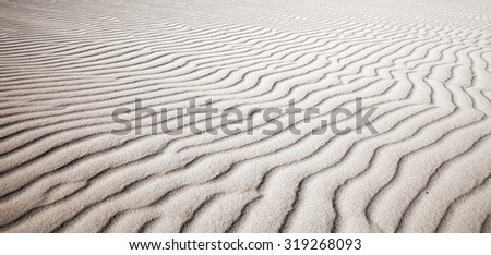 sand and wind pattern on dune surface natural background - stock photo