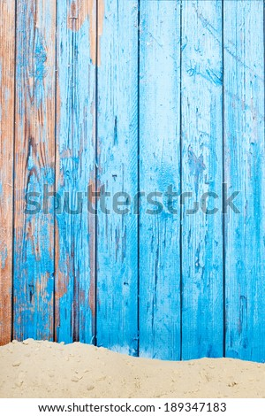 Sand at the beach with wooden blue vintage background - stock photo