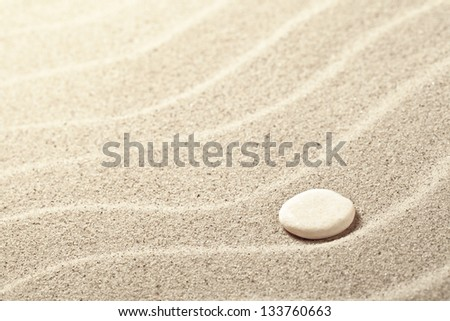 Sand background with white stone. Sandy beach texture - stock photo