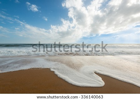 Sand beach with waves and blue sky in Albufeira, Portugal - stock photo