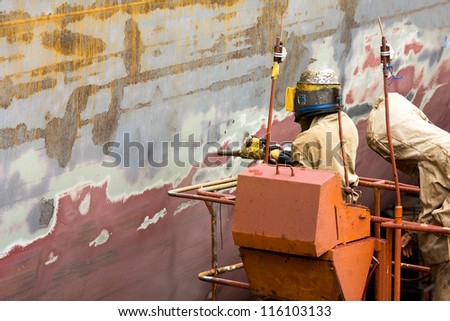 Sand blasting of the container ship's hull on the dry dock. - stock photo
