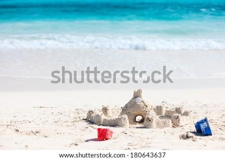 Sand castle and beach toys at tropical coast - stock photo