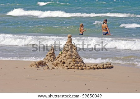 Sand castle and two young girls in the sea in background - stock photo