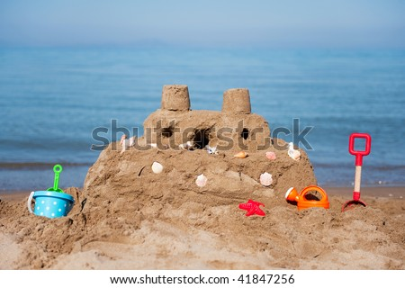 sand castle at the beach with plastic toys - stock photo
