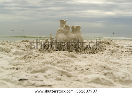 Sand castle on tropical beach with dark stormy sky background - stock photo