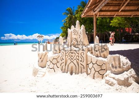 Sand castle on white tropical sandy beach - stock photo