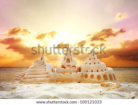 Sand Castle over Sunset on the Beach - stock photo