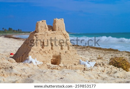 Sand castle with shells built on summer tropical beach - stock photo