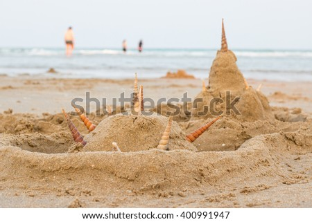 Sand castles on the beach with shell - stock photo
