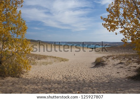 Sand dune in the autumn, with hiker in distance - stock photo