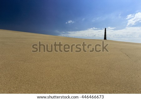 Sand dune near Memory beach from the north of Portugal against blue sky with some interesting light and clouds seeing his iconic granite obelisk - stock photo