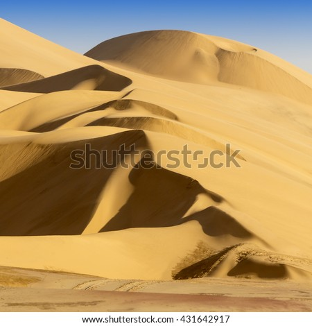 Sand dunes and shadows in a desert landscape - stock photo