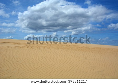 sand dunes blue sky and fluffy clouds - stock photo