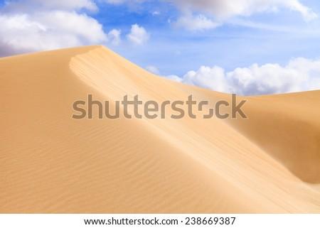 Sand dunes in Boavista desert with blue sky and clouds, Cape Verde - Cap Vert - stock photo
