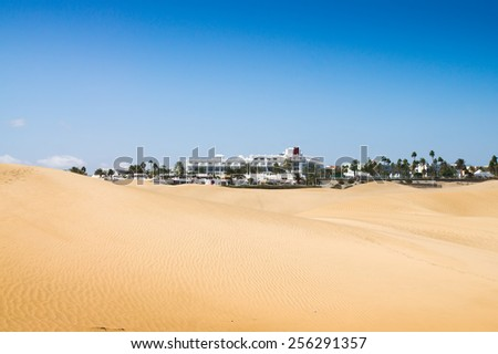 Sand dunes in sunny day. Beautiful white hotel in the background. Canary islands, Maspalomas. Spain.  - stock photo