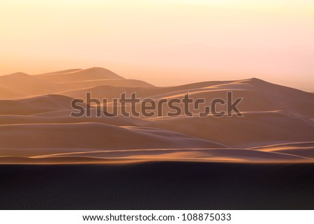 Sand Dunes of Colorado in Sandstorm Depiction of the mystery of the winds and sand. The story written one day and changed by the next. Elusiveness illuminated just before the light flickers out.   - stock photo