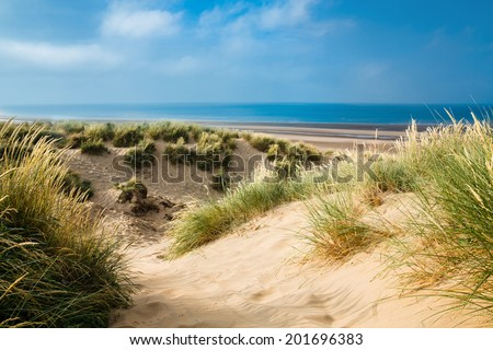Sand dunes with sea in background on a sunny day in summer - Camber Sands, East Sussex, England - stock photo